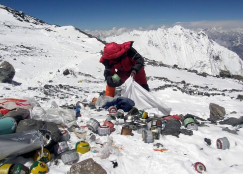 A Nepalese Sherpa picking up litter near the summit of Mt. Everest.