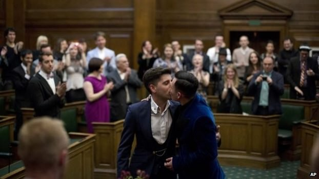 A gay couple officially married in the council chamber at Camden Town Hall in London, England.
