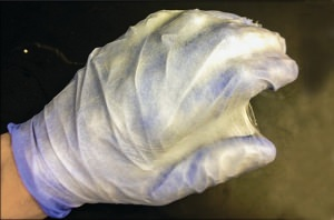 A demonstration of the nano-fiber spray, showing its ability to form a mat that conforms to the shape it lands on, in this case a gloved hand.  (Image courtesy of C&EN)