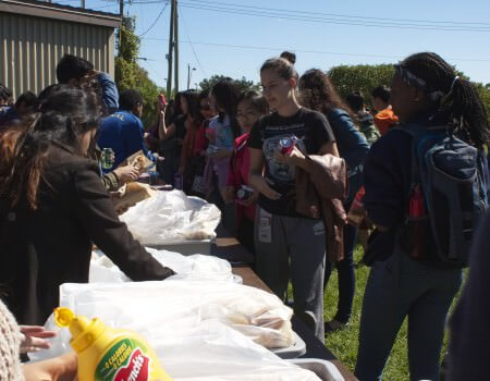 Grade 9 students waited in line to receive lunch at the barbecue.