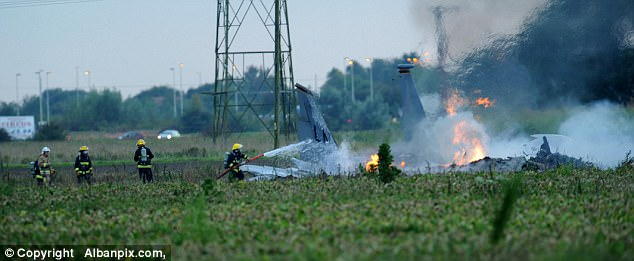 Firefighters and emergency vehicles at the scene of the crash putting out the flaming aircraft and sealing off the area.