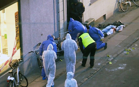 Officials investigate the aftermath of Saturday's first shootings. (Image courtesy of The Telegraph.)