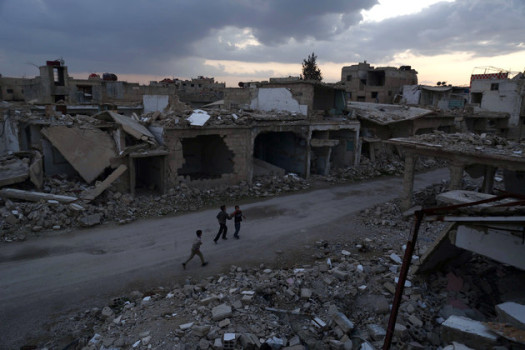 Syrian children walk past heavily damaged buildings in the rebel-held town of Douma, on the eastern edges of the capital Damascus on February 27, 2016, on the first day of the landmark ceasefire agreement. Less than a day into a landmark ceasefire deal in parts of the country, residents say their usual routine has been thrown off without the usual sounds of artillery, rocket attacks, or helicopter-borne barrel bombs. / AFP / Sameer Al-Doumy (Photo credit should read SAMEER AL-DOUMY/AFP/Getty Images)
