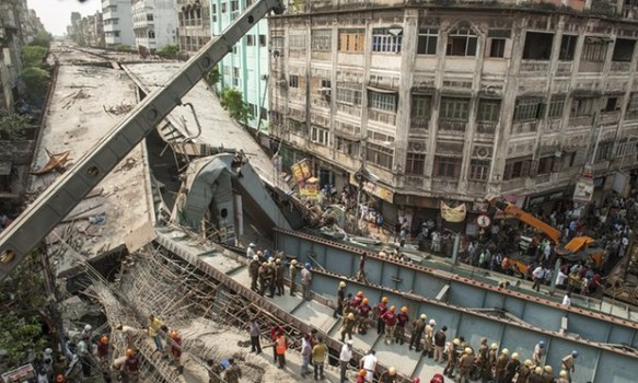 Many look on as workers rescue those trapped under the rubble (Source: The Guardian)