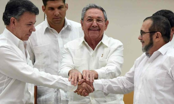 "President Juan Manuel Santos and Rodrigo ""Timochenko"" Londoño, the leader of the Revolutionary Armed Forces of Columbia, shake hands at peace talks in Havana. (Image courtesy of The Guardian)"