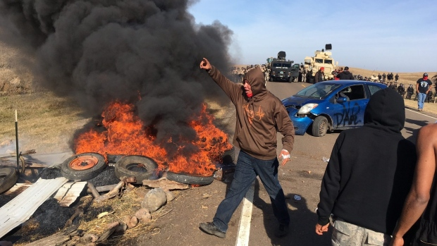 Demonstrators stand next to burning tires as armed soldiers force protestors of the private land (Courtesy of: Mike McCleary/The Bismarck Tribune/Associated Press)