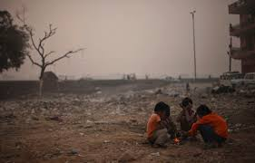 Indian boys sit around a fire in one of the most polluted area in the world. (Image courtesy of Mashable)
